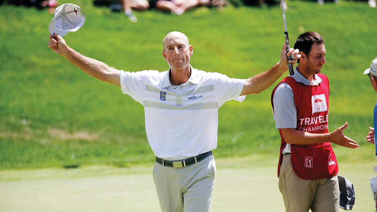 Jim Furyk raises his arms and keeps a tight grip on the ball that he hit 58 times on Sunday, August 7, setting a record for fewest strokes ever taken in a round of PGA golf.