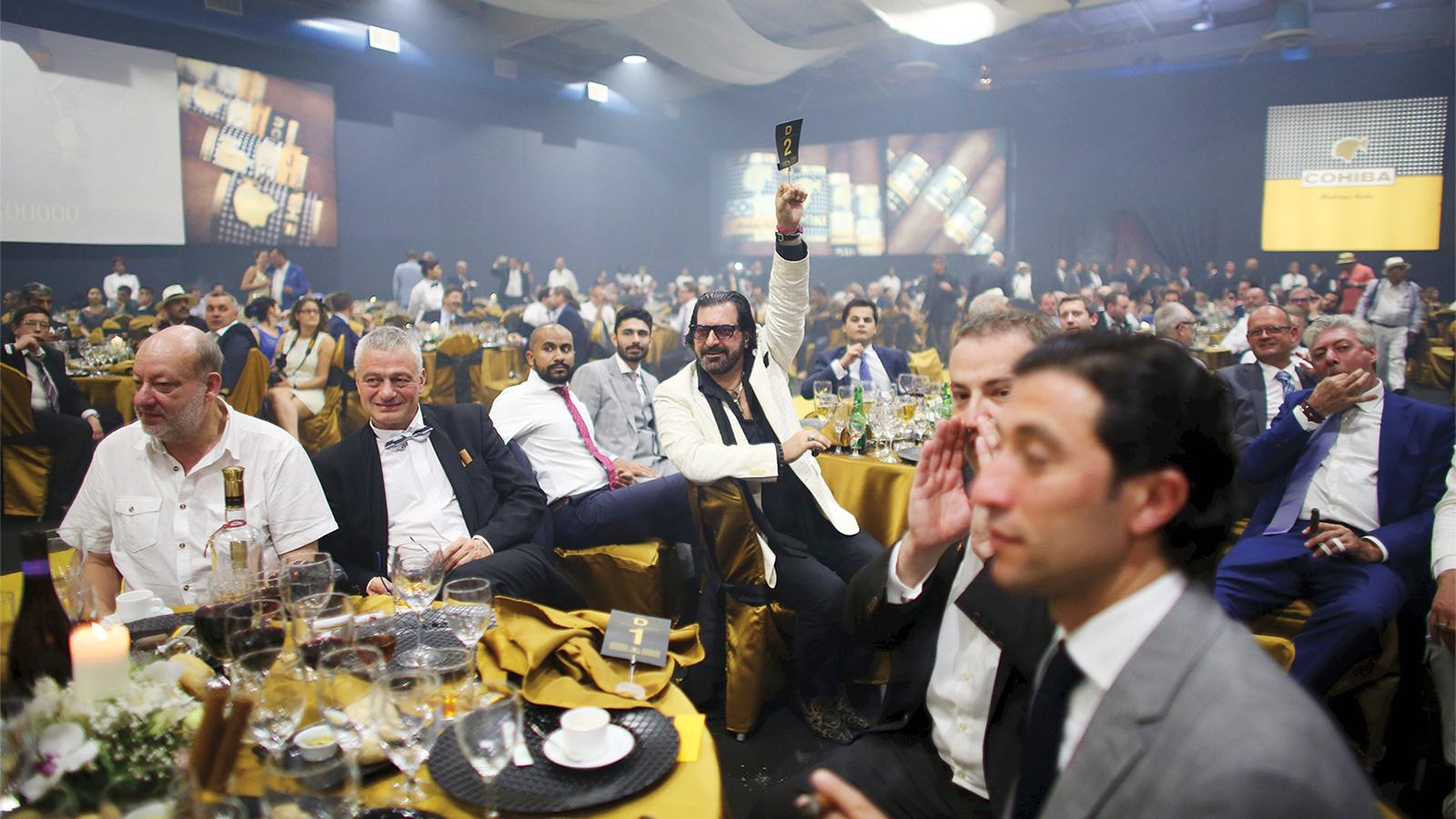 Reza Balouds from Iran (center) raises his bid for a limited-edition Cohiba humidor during an auction at the gala dinner of the XVIII Habanos Festival.