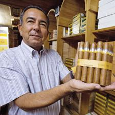 Abel Expósito Diaz, who runs the shop at the Partagás Cigar Factory, shows off a selection of Cohiba Siglo VI cigars.