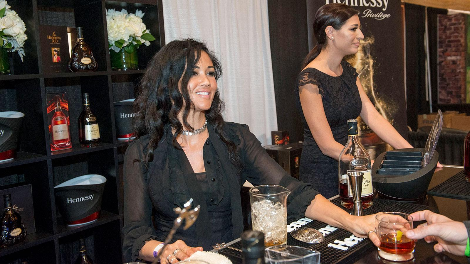Isidra Suga from Hennessy pours drinks for thirsty smokers.