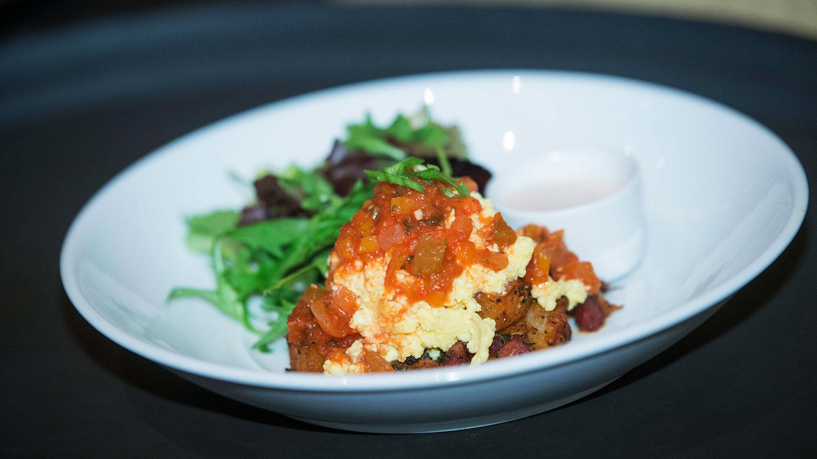 Brisson's dish of Tchoupitoulas Hash, soft scrambled eggs, creole sauce and a small salad of greens.
