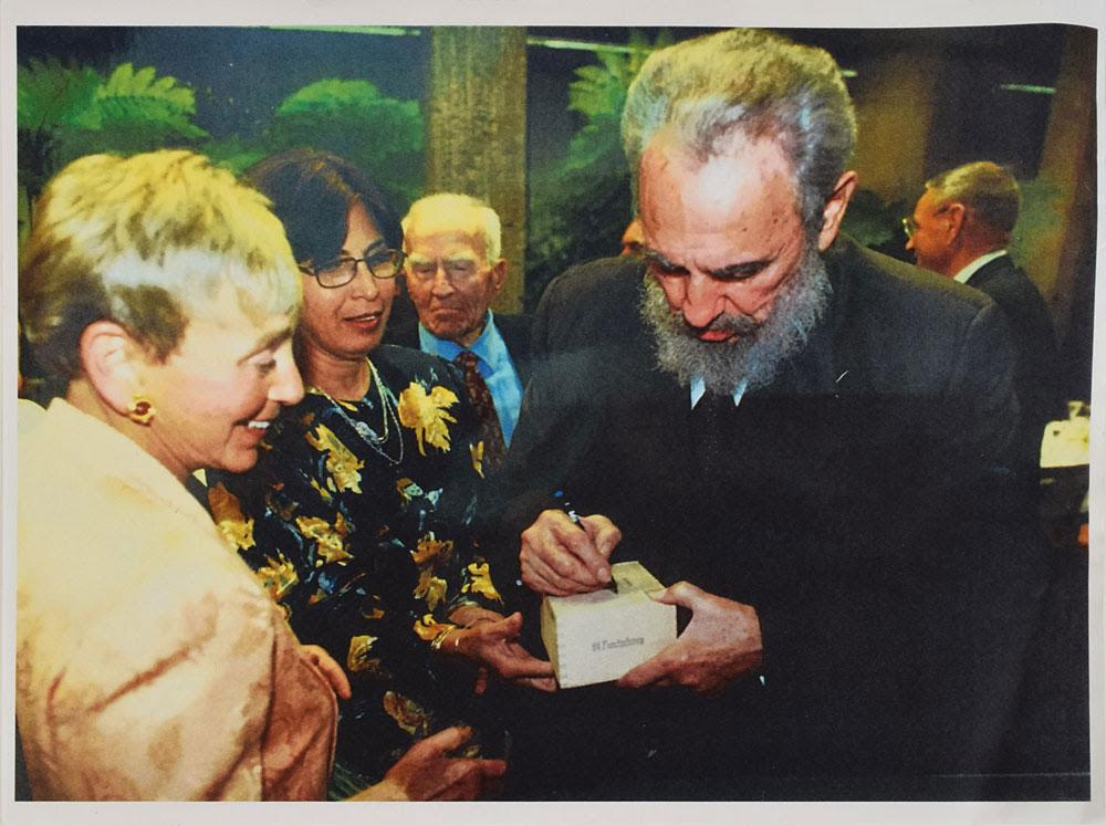 Castro, right, signing the box of Trinidads before presenting it to philanthropist Dr. Eva Haller, left.