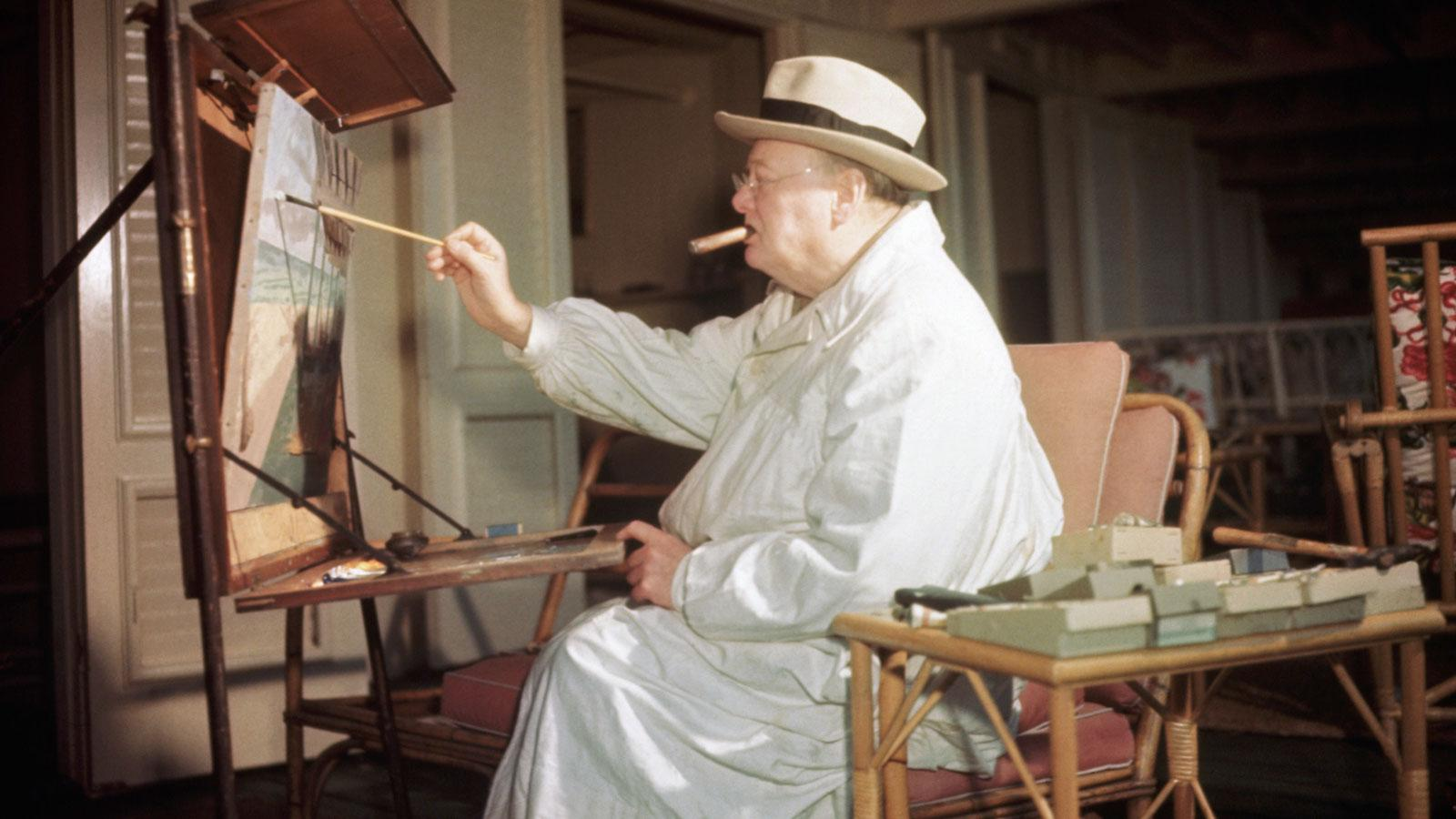 Sir Winston Churchill relaxes while smoking and painting in his art studio.