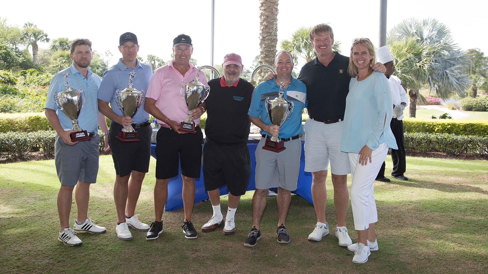 Marvin R. Shanken, center, and Ernie and Liezl Els, far right, present trophies to the winning groups.