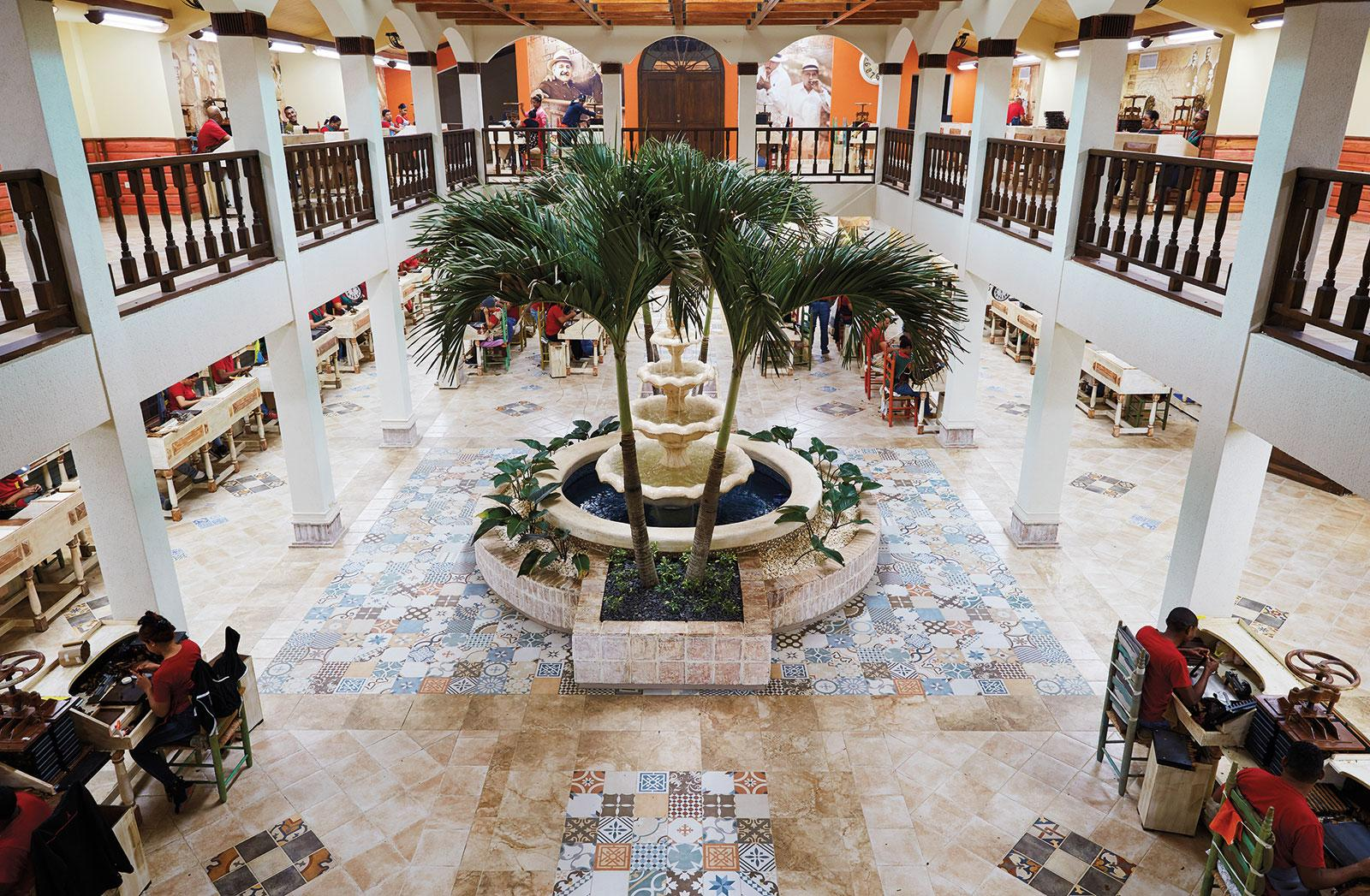 "A view from the upper level of the grand courtyard. The fountain brings a tranquil air as rollers make cigars on both floors of the ""cathedral of tobacco."""