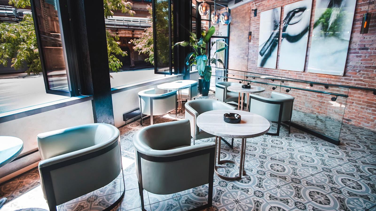 Enjoy the gray-green leather chairs at the marble tables next to the open windows.