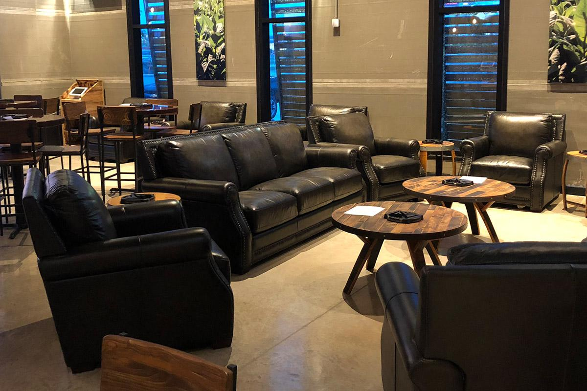 The expansive indoor lounge features plush leather chairs and bar tables.