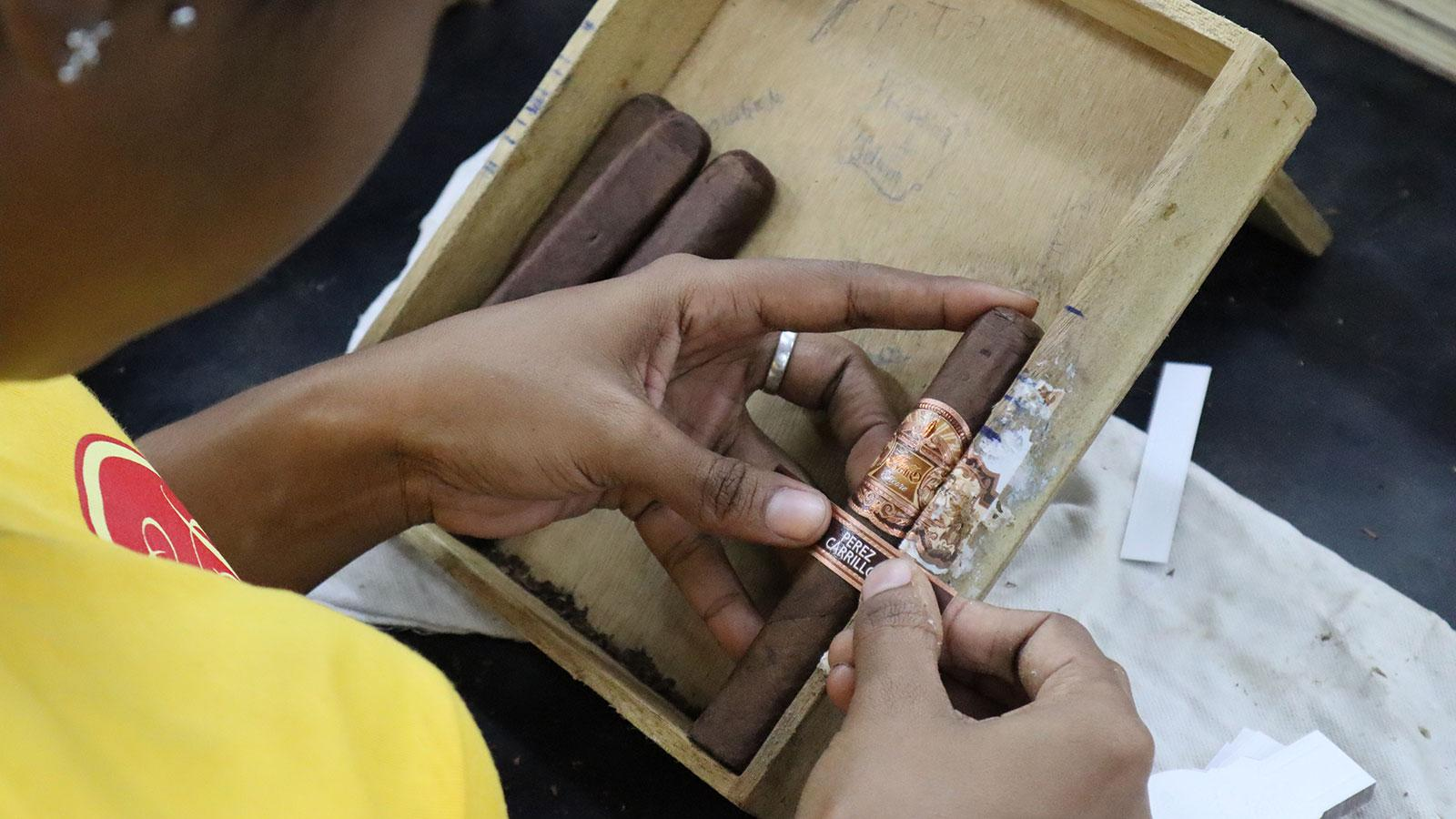 Encore cigars being banded inside EPC Cigar Co.'s La Alianza factory checks color consistency.