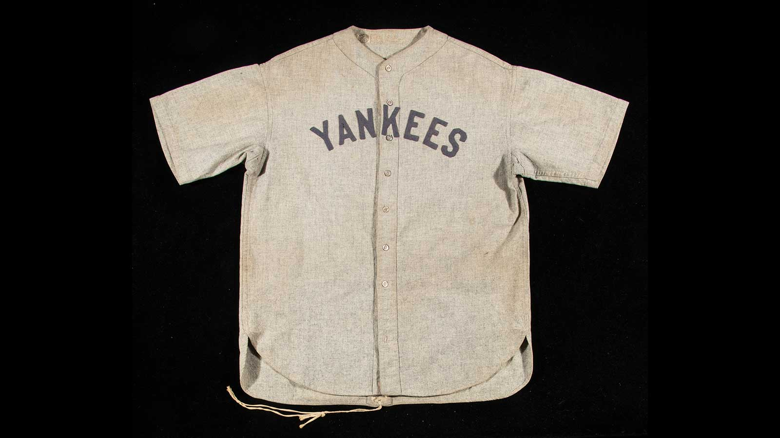 "The intact, light grey flannel shirt bears its original drawstrings at the back, all of its buttons, and the name ""Ruth"" stitched into the collar. ""Yankees"" is bannered across the chest."