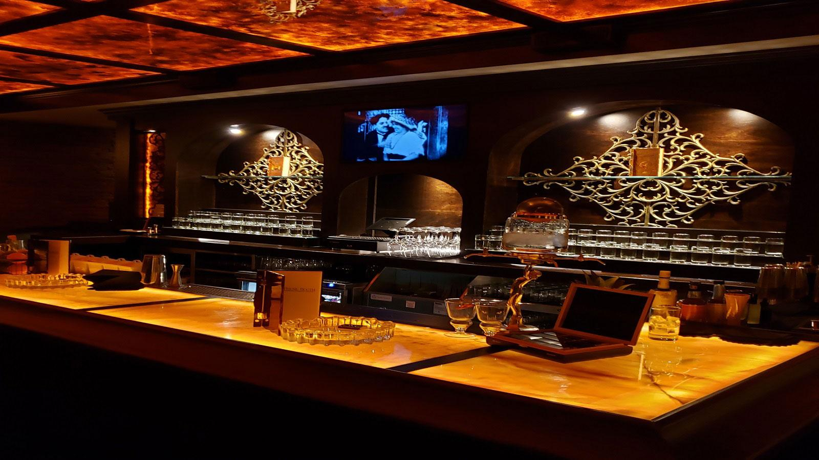 The honey-onyx bar is the focal point of the room, where drink mixing is raised to an art form.