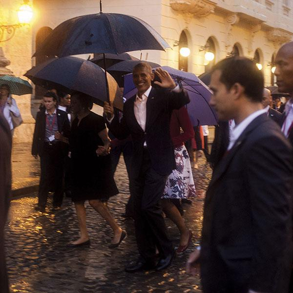 U.S. President Barack Obama, center, waves as he walks in heavy rain during his visit to Havana, Cuba.