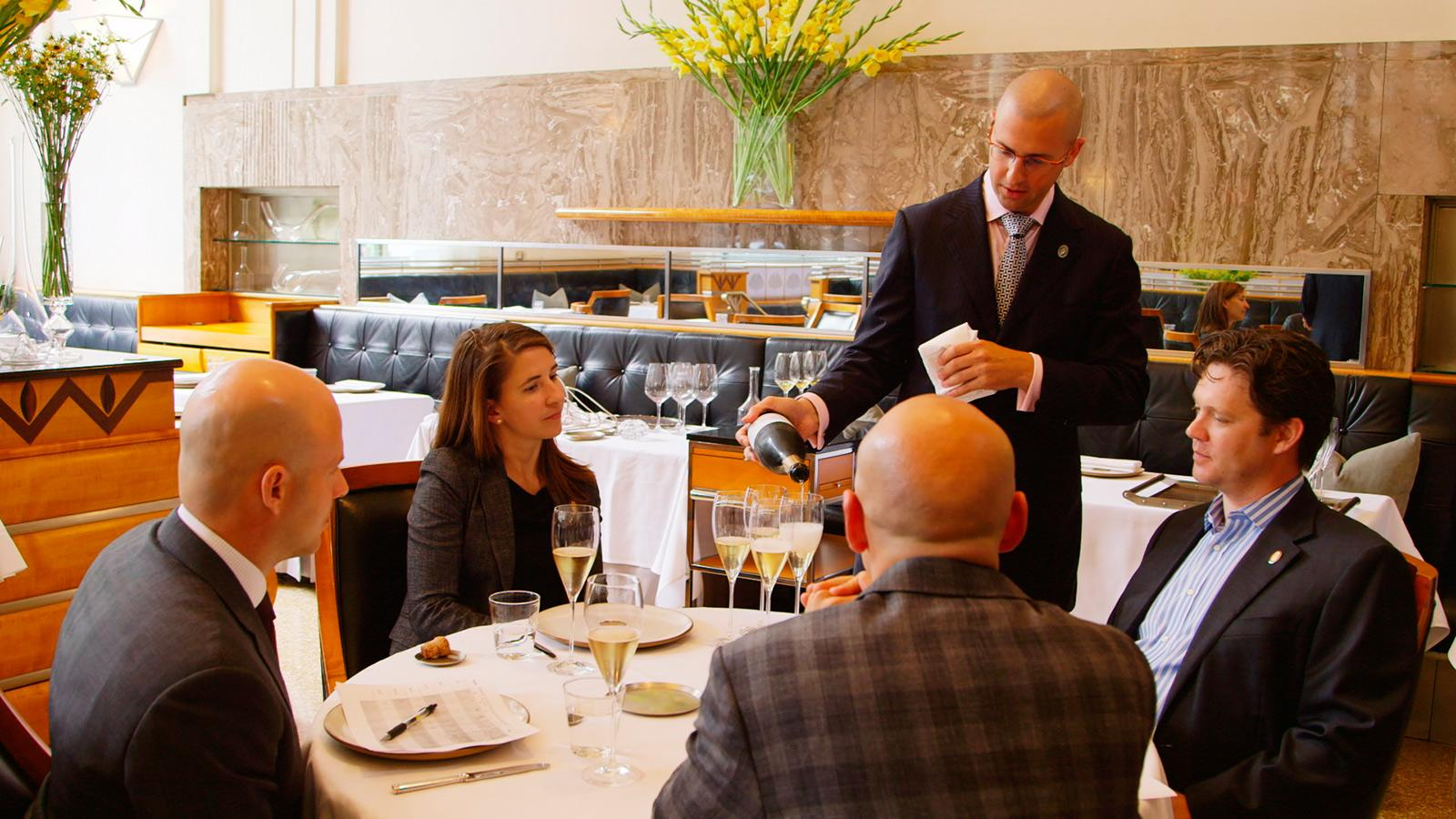MS candidate Josh Nadel (standing) attempts to serve equal pours to Master Sommeliers Dustin Wilson, Laura Maniec, Geoff Kruth and Sabato Sagaria.