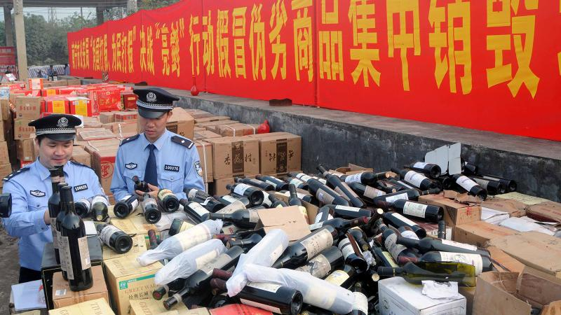 Chinese police destroy confiscated counterfeit wines in the Guangxi Zhuang region during a 2011 raid.