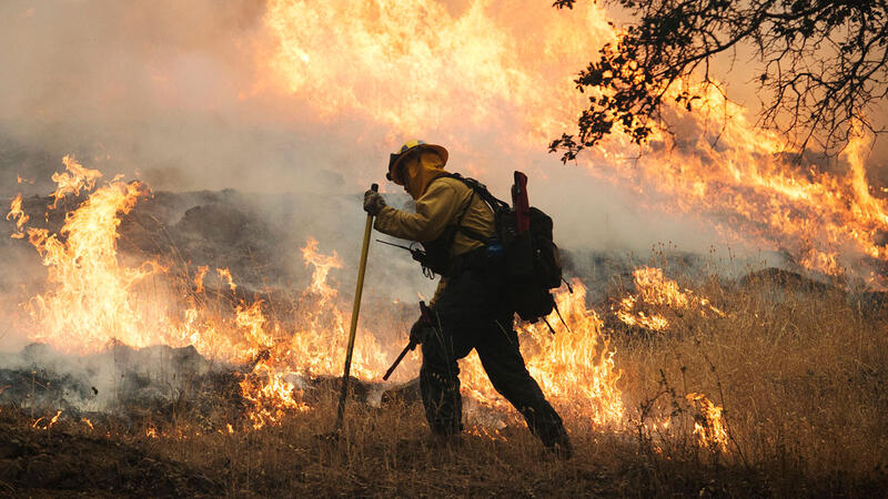 A firefighter sets a back burn along Highway 29, hoping to establish the road as a firebreak.