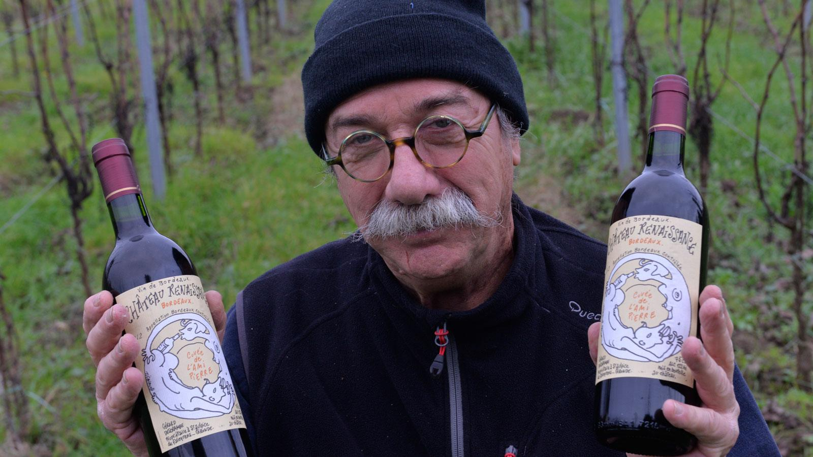 Bordeaux winemaker Gérard Descrambe holds up a Château Renaissance wine bottle with a label designed by the Charlie Hebdo cartoonist known as Tignous, killed in the terror attack.