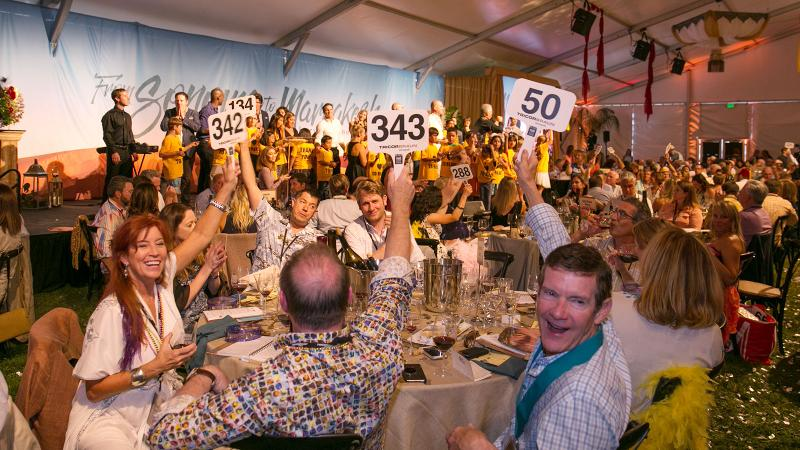 Bidders compete at the Sunday live auction for top lots, including exclusive dinners with winemakers.