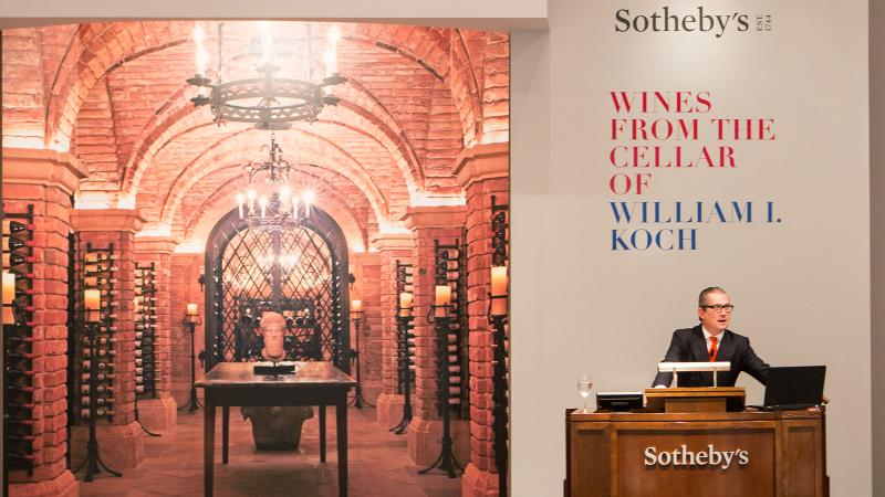 With an image of Bill Koch's cellar behind him, Jamie Ritchie of Sotheby's oversaw bidding in New York; the auction brought in $21.9 million.