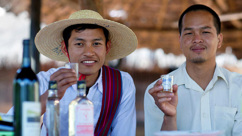 Two Intha tribal members in Myanmar sample a local wine, made by an industry that now faces foreign competition.