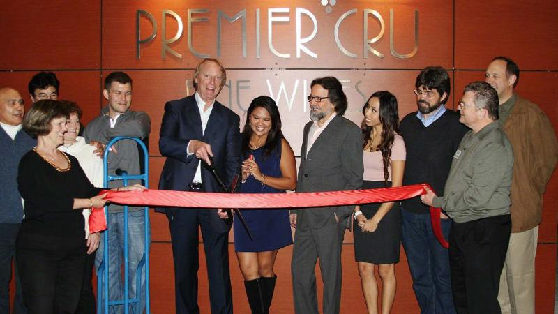 John Fox (with scissors) cuts the ribbon at the opening of Premier Cru's new location in 2011.