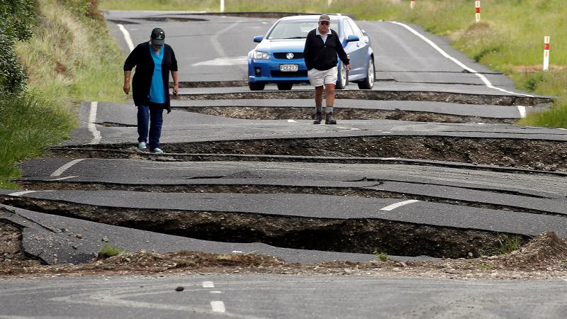 Motorists examine road damage on a highway south of Blenheim after New Zealand's recent earthquake.