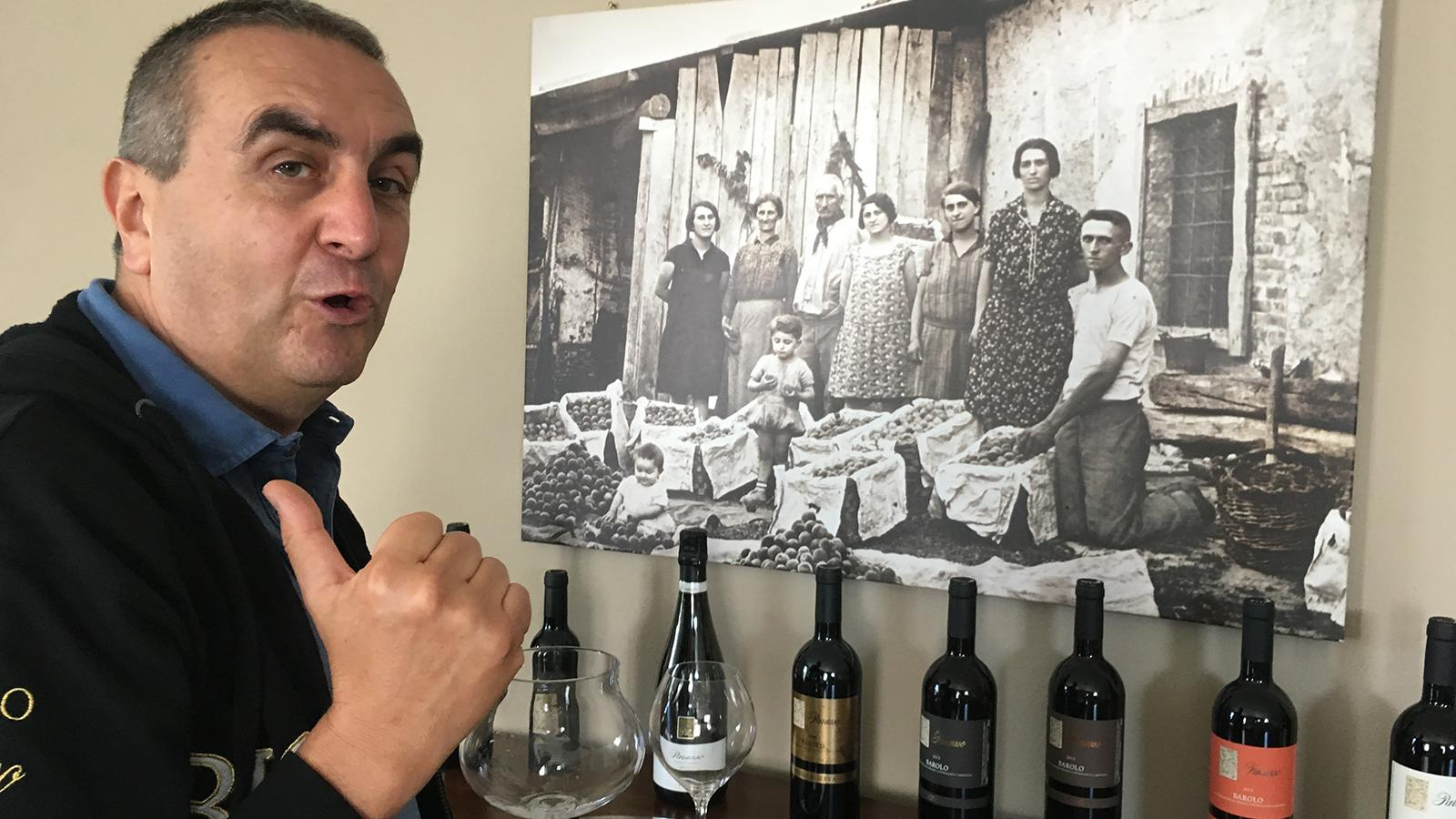 Marco Parusso with a photograph of his family from 1930. The young child standing is Marco's father and winery namesake Armando Parusso.