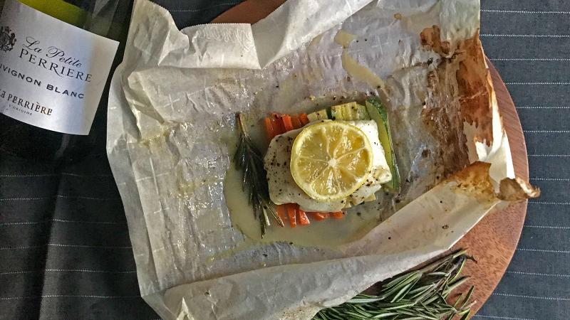 Steaming the fish in the oven with white wine and lemon creates a juicy fillet while flavoring the vegetables.