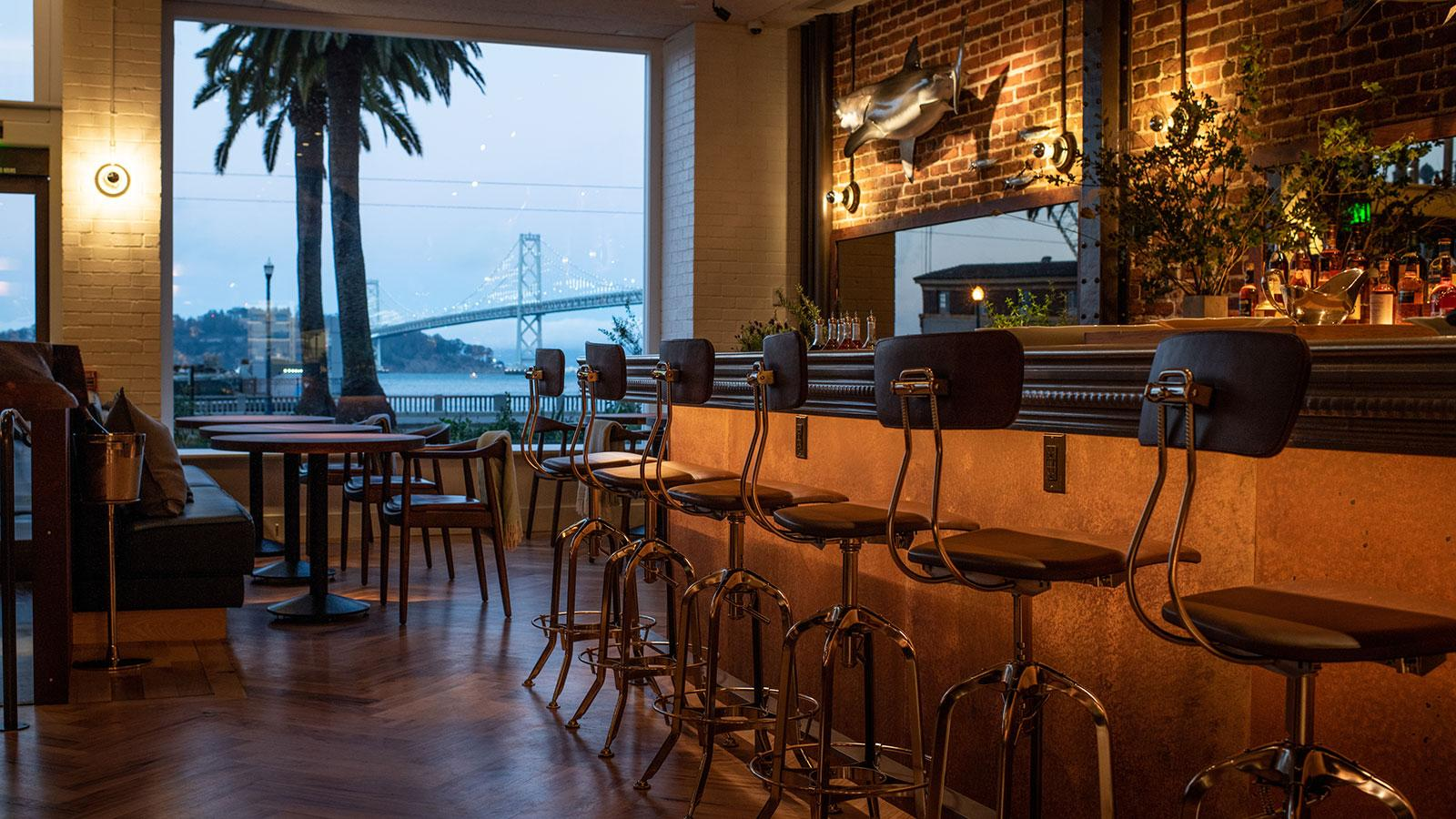 A seat at the bar includes a view of the Bay Bridge.
