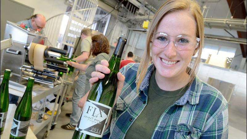 Kaleigh Flynn shows off a bottle of wine made by students at Finger Lakes Community College.