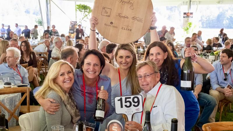 Several vintners celebrate their winning bid on a barrel lot.