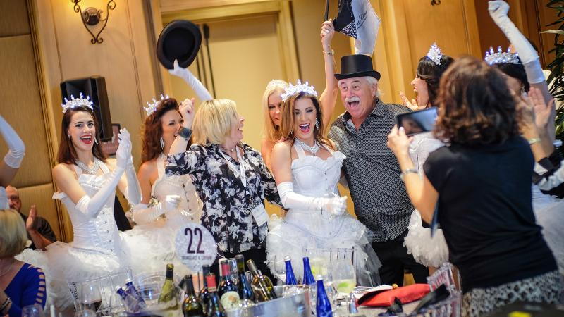 Winning bidders at the live auction celebrate; for 10 years, the event has raised money to help local schools and children's health charities.