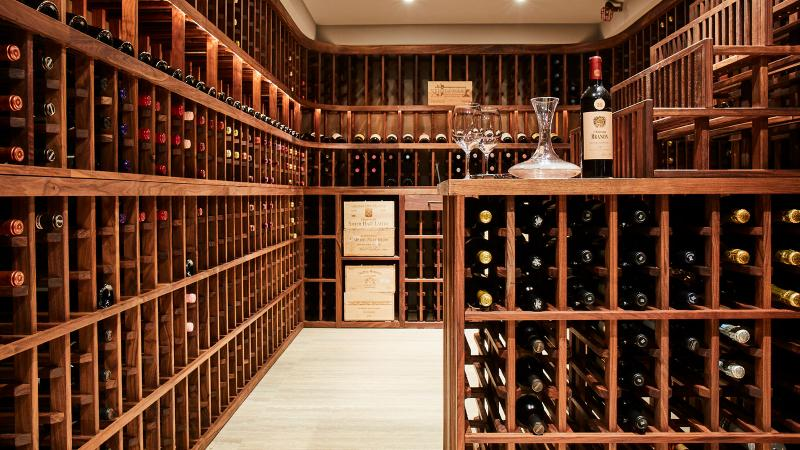 Image for an article: Lev Spiro's basement cellar houses close to 600 bottles on shelving made from olive oil–coated walnut.