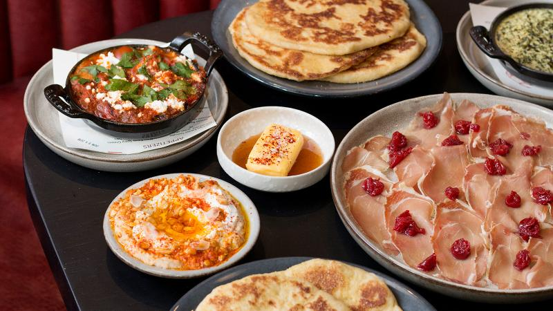 Kōjin, the latest from the Momofuku group, serves their corn flatbread with accoutrements like spinach dip, Niagara ham and fire-roasted tomatoes with feta cheese.