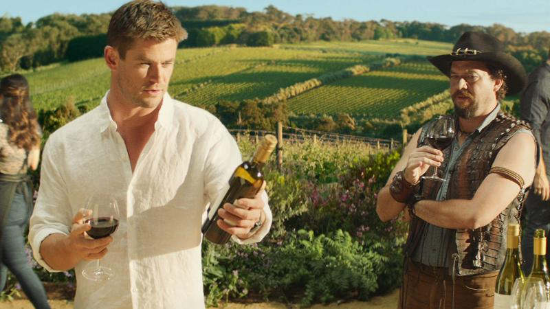 Chris Hemsworth (L) and Danny McBride ponder opening a bottle with a comically oversized saber.