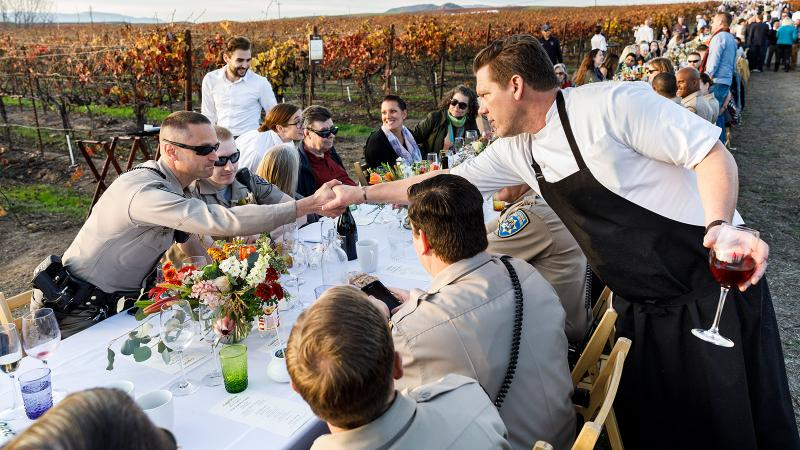 Chef Tyler Florence (right) supports local wines (far right) and greets first responders at a benefit dinner in the film.
