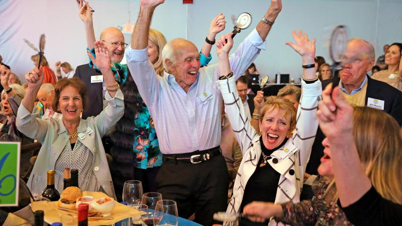 Festival trustees Don and Darlene DeMichele, center, celebrate during the live auction action.