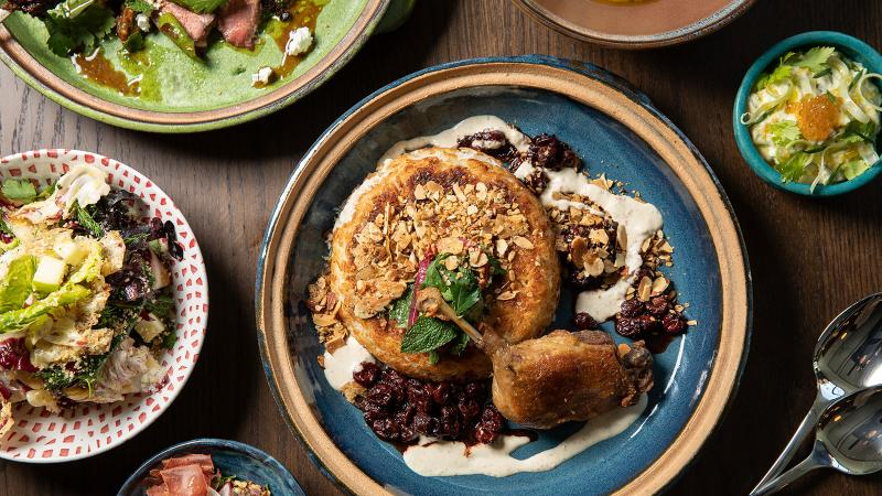 Image for an article: Cira's duck leg confit with crispy rice, sour cherries and toasted almonds