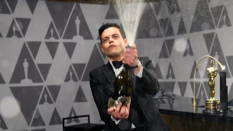 Image for an article: Is this the real life? Is this just fantasy? Rami Malek pops Piper-Heidsieck after his big win.