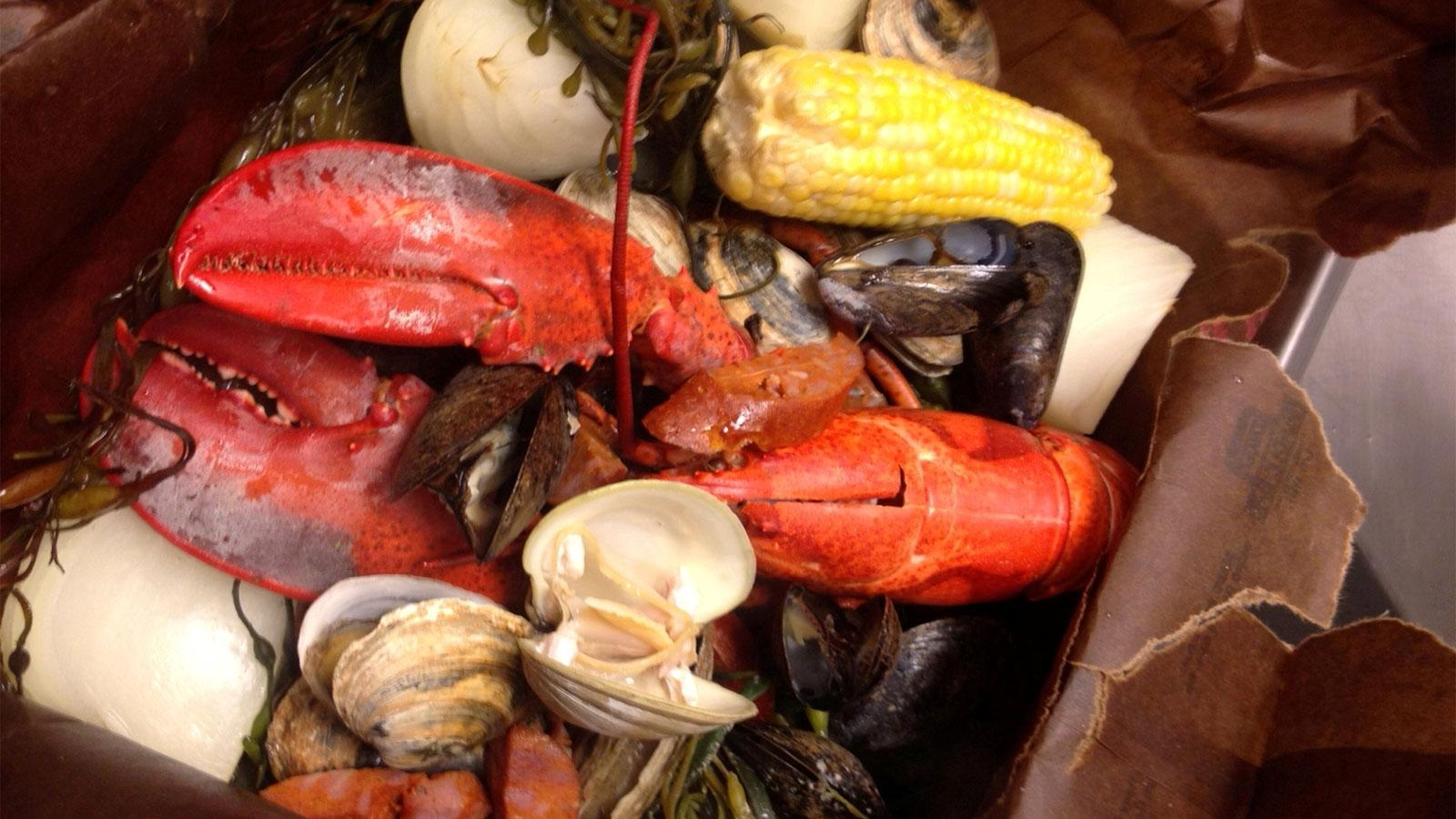 Lobster, clams, sausage, corn and potatoes bake together in a paper bag.