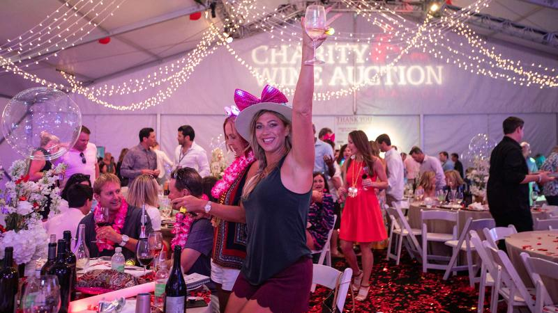 Auction guest Suzi Stanley raises a glass for local charities; Destin has become one of the country's top events in recent years.