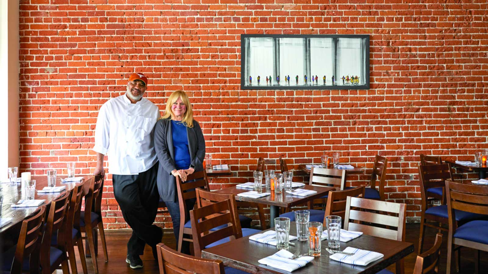 The two owners standing in front of a brick wall in their restaurant