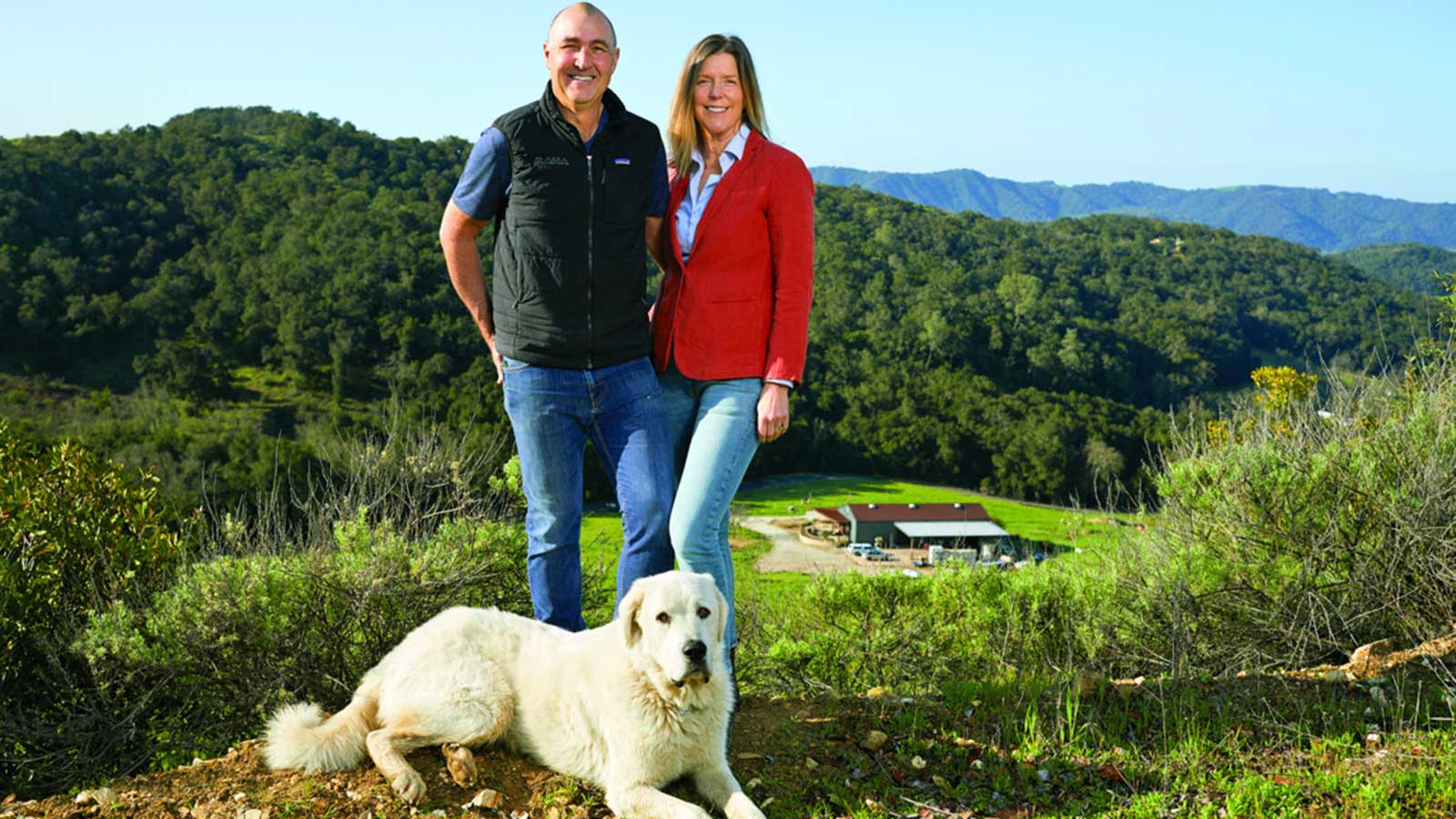 The owners with a large white dog at their feet