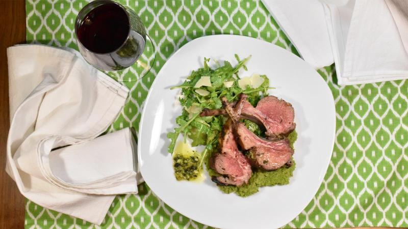 A plate of lamb chops, minty mashed peas and salad, with a glass of red wine