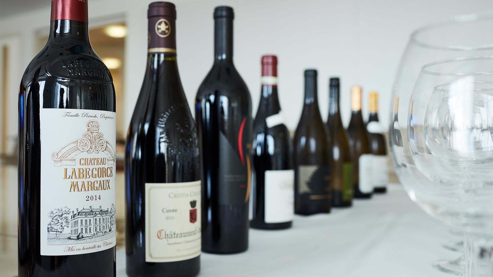 A collection of wine bottles to be shared includes Bordeaux and Châteauneuf-du-Pape reds.