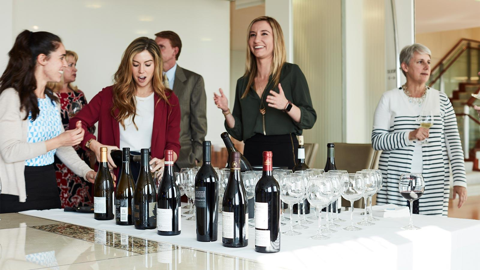 Group of law firm employees gathered for a wine tasting, with bottles and glasses on a table.