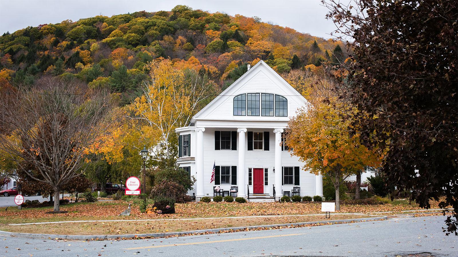 The exterior of Four Columns Inn, with fall-colored foliage in the background
