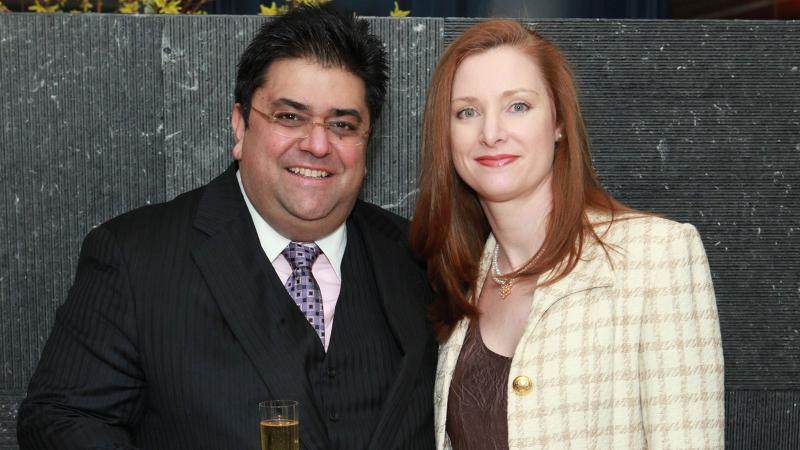 Omar Khan and his wife, Leslie, at a charity wine auction—one lawsuit accuses her of helping him cheat investors.