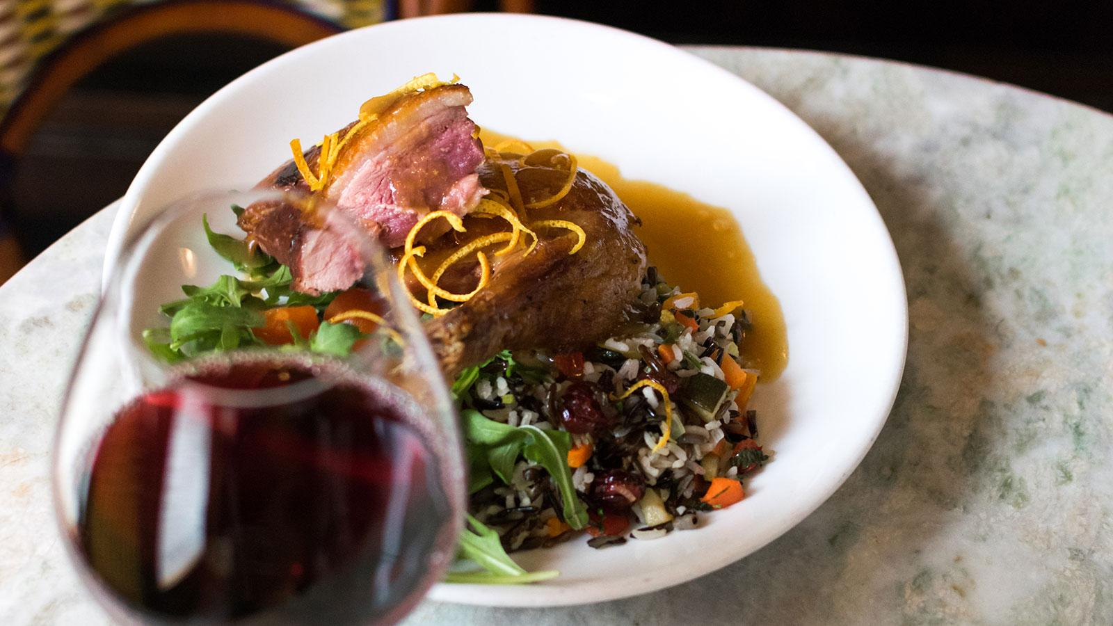 Duck dish with red wine in the foreground