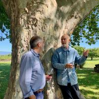 John Malkovich shares a glass with his winemaker, Jean Natoli (left).