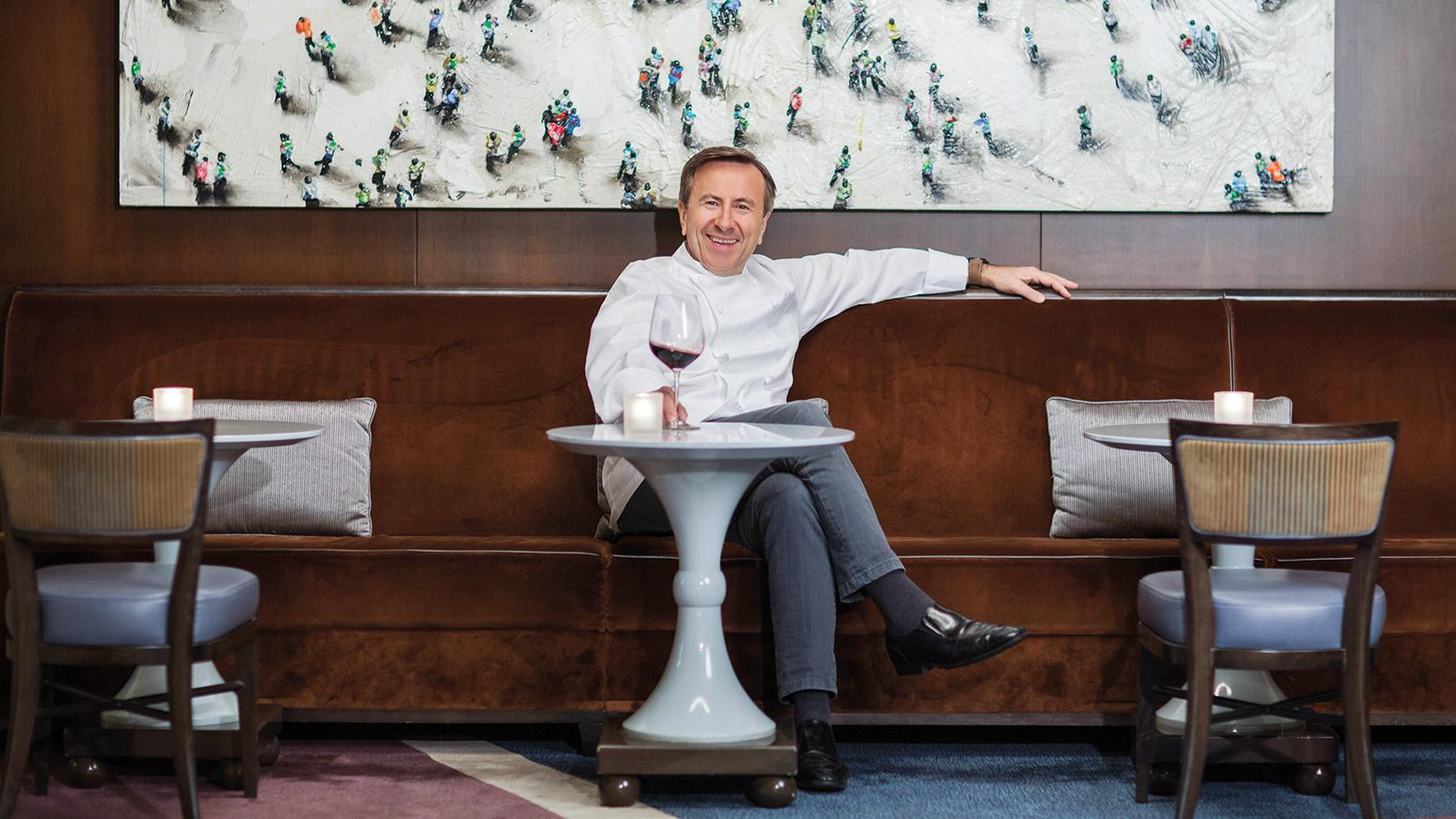 Chef Daniel Boulud at a table in his restaurant with a glass of wine
