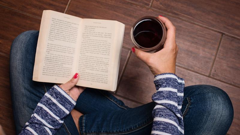 Woman with wine and book